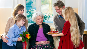 Grandma gets a birthday cake from loving family.